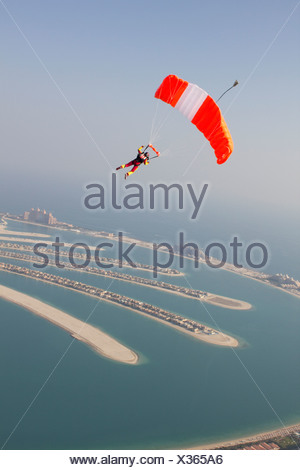 Woman parachuting over rural landscape - Stock Photo