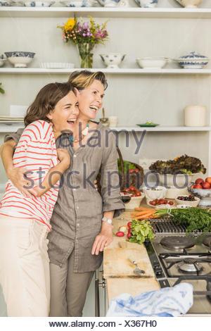 Senior woman hugging daughter in kitchen - Stock Photo
