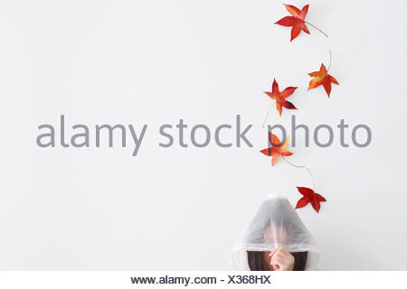 Autumn leaves falling on a woman wearing a raincoat - Stock Photo