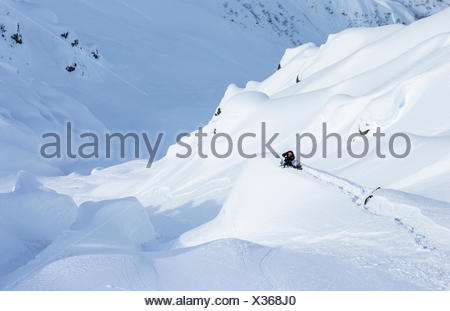 A snowboarder filmer sets up on a snow covered rock and crouches behind his camera to get a shot on a sunny day in Haines, Alaska. - Stock Photo