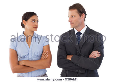 Smiling co workers looking seriously at each other on white background - Stock Photo