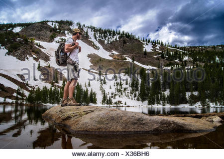 USA, Colorado, Indian Peaks Wilderness, Hiker looking at view - Stock Photo