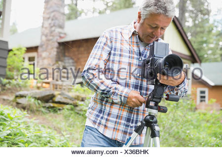 Middle-aged man adjusting lens of SLR camera in yard - Stock Photo