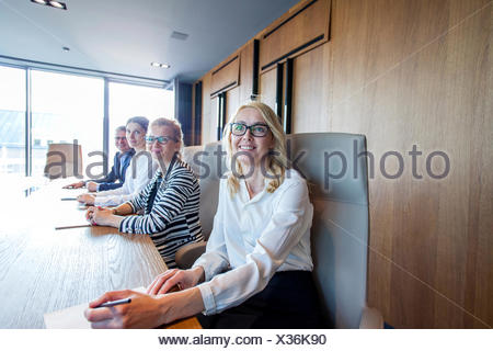 Business people sitting at conference table in board room - Stock Photo