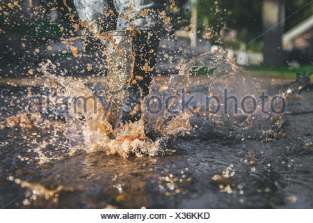 Close-up of child's legs splashing in a puddle of water - Stock Photo