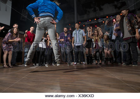 Crowd cheering and watching dancers in nightclub - Stock Photo