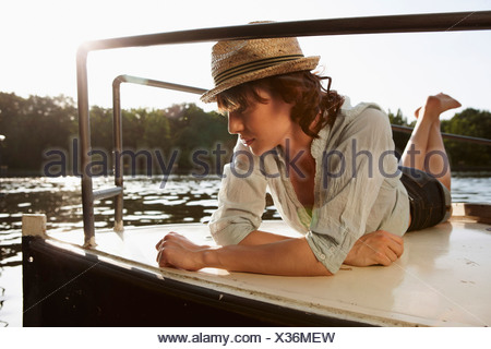 Germany, Berlin, Young woman lying on motor boat - Stock Photo
