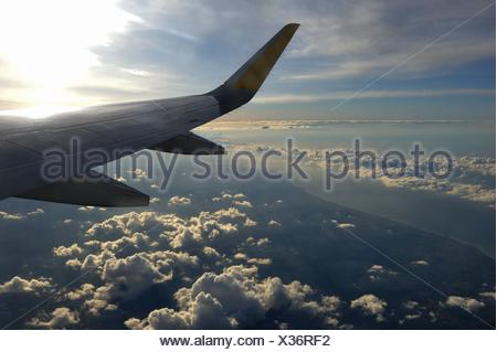 aircraft wing in flight over the clouds. - Stock Photo