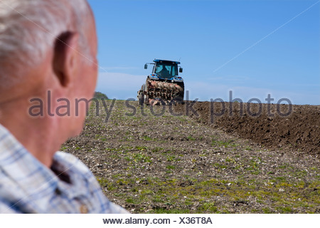 Close up of farmer watching tractor and plough in field - Stock Photo