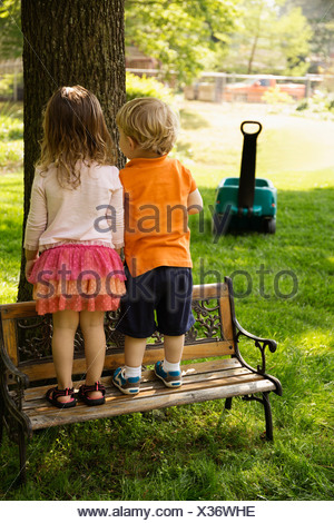 Male and female toddler friends standing on scaled park bench - Stock Photo