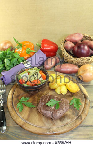 roasted ostrich steak with baked potatoes - Stock Photo