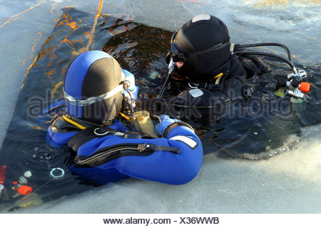 ice diver preparing to dive into frozen lake, Germany, North Rhine-Westphalia, Steinbach-Talsperre, Euskirchen - Stock Photo