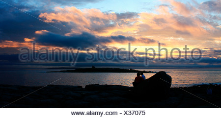 Doolin Harbour, Co Clare, Ireland; Couple watching the sunset with Aran Islands in the background - Stock Photo