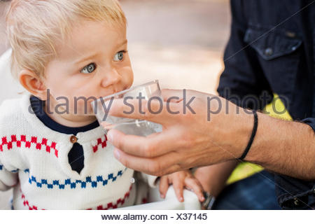 Midsection of father feeding water to baby girl in park - Stock Photo