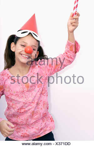 smiling girl playing with a blowpipe - Stock Photo