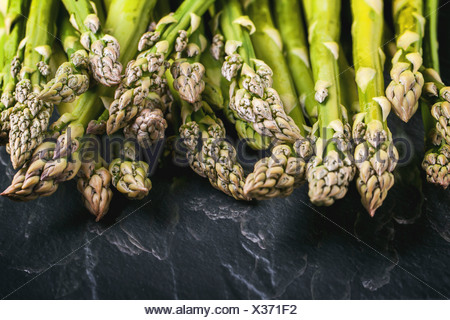 Young green asparagus on black glass. - Stock Photo