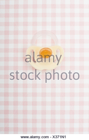 Pacifier on pink checker pattern - Stock Photo
