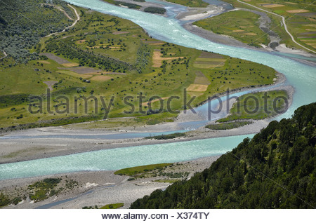 Reting river, Reting Tsangpo, with centuries-old juniper trees in the mountains of Reting Monastery, Mount Gangi Rarway - Stock Photo