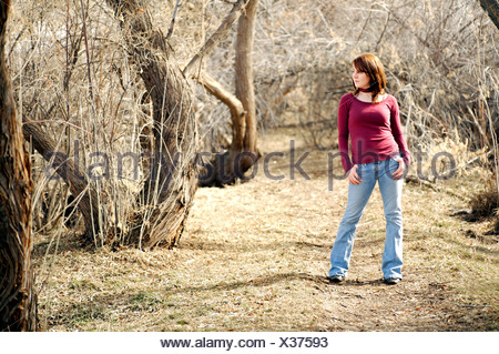 Young woman posing in a wooded area - Stock Photo