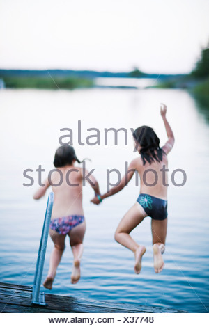 Two girls on a jetty Sweden. - Stock Photo