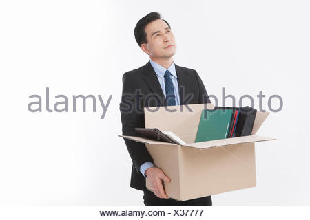 Middle aged businessman carrying files in a box looking up - Stock Photo