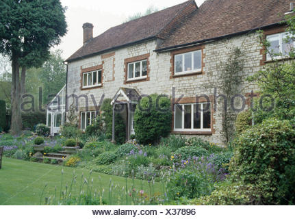 Lawn and flower borders in front of18th-century stone farmhouse - Stock Photo