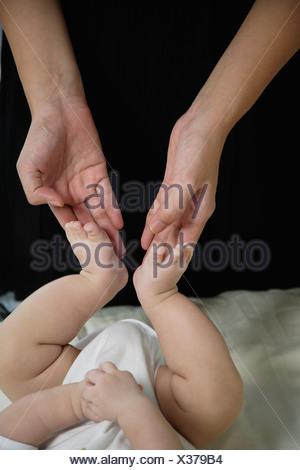 Woman touching baby's feet - Stock Photo