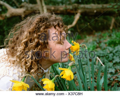 Woman smelling daffodils - Stock Photo