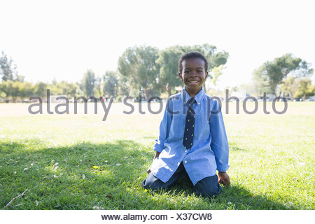 Portrait of boy kneeling on grass in sunlit park - Stock Photo