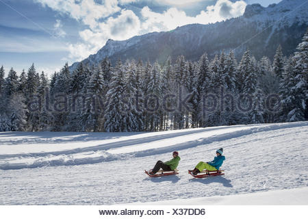 Germany, Bavaria, Inzell, couple on sledges in snow-covered landscape - Stock Photo