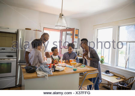 Family surprising mother with birthday cake in kitchen - Stock Photo