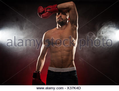 Boxer wiping his brow during a fight as he stands in his corner to clear sweat from his eyes in a smoky atmosphere - Stock Photo