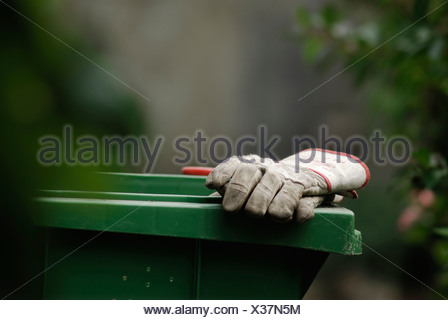 Work gloves resting on the edge of a green organic waste bin - Stock Photo