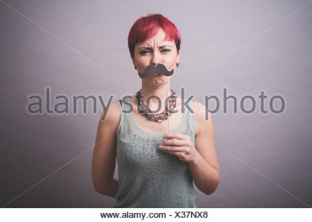 Studio portrait of confused young woman holding up mustache in front of face - Stock Photo