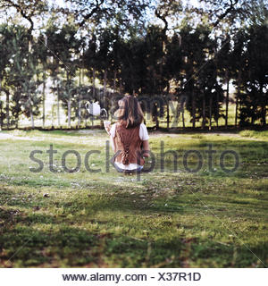 Rear view of woman sitting in park with floating teacup pouring tea - Stock Photo