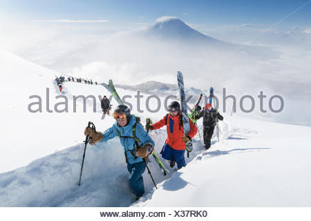 With Mount Yotei in the background, a team of backcountry skiers, led by a woman, are hiking to the summit of mount Annupuri, near ski resort Niseko United on the Japanese island of Hokkaido.     The skis they carry are big and wide allowing the winter en - Stock Photo