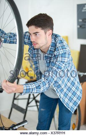 mechanic serviceman adjusting bicycle gear on wheel in workshop - Stock Photo