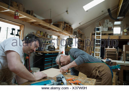 Carpenters examining wood board in workshop - Stock Photo