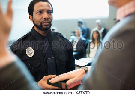 Male bailiff holding bible for witness in legal trial courtroom - Stock Photo