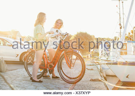 Sweden, Blekinge, Hallevik, Two teenage girls(14-15, 16-17) with bicycles standing at marina bay on sunny day - Stock Photo