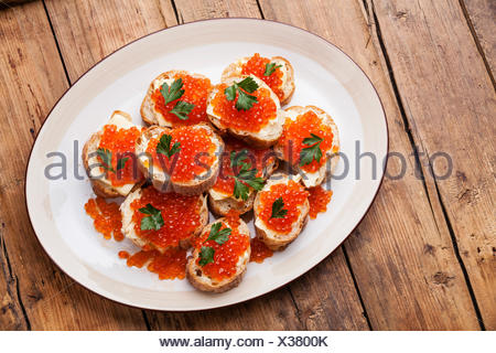 Sandwiches with Salmon red caviar and parsley on white plate on wooden background - Stock Photo