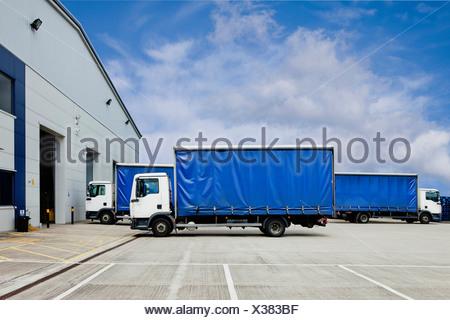 Trucks parked outside distribution warehouse - Stock Photo