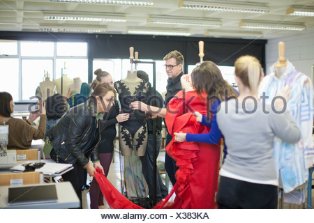 Fashion design teacher and students in class - Stock Photo