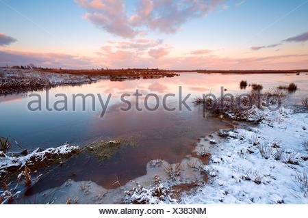 sunrsie over river in winter - Stock Photo