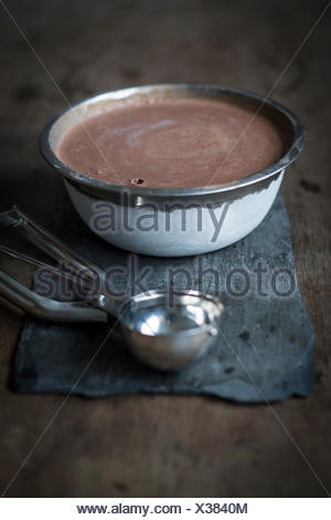 Home made chocolate ice cream in steel bowl on slate board on wooden table - Stock Photo