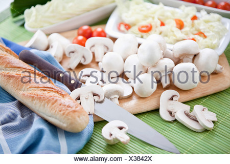 Sliced mushrooms on chopping board, close-up - Stock Photo