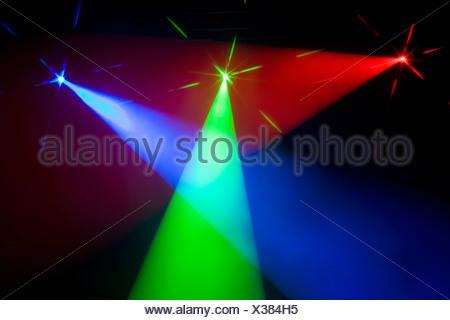Three multi colored spotlights crossing light beams - Stock Photo