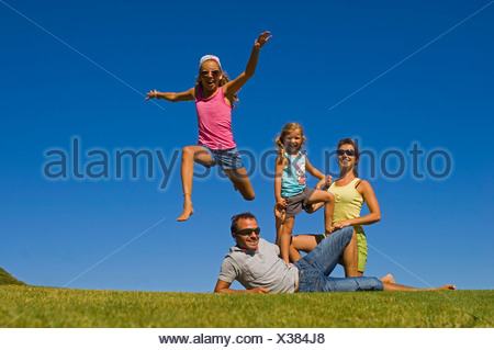 young family with two little daughters posing on a lawn in front of a cloudless blue sky, France - Stock Photo
