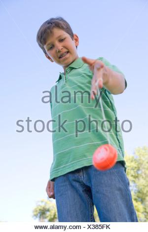 Young boy using yo yo outdoors smiling - Stock Photo