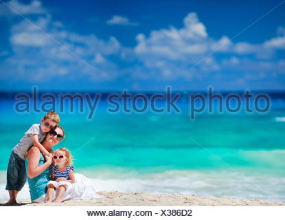 young mother and her daughter sitting on sandy beach, her son embracing her - Stock Photo